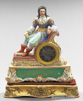 """This Paris porcelain """"Troubadour"""" mantel clock was made about 1875. It is named for the elaborately costumed entertainer seated at the top. It has the typical Paris porcelain polychrome and gilded decoration. (photo credit: New Orleans Auction Galleries)"""