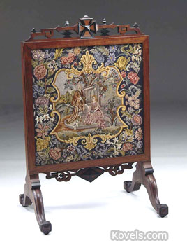 This is a cheval screen used to hide an unused fireplace. It is walnut with a needlework screen. The 41-inch-high screen sold last year for $460 at a James Julia auction in Fairfield, Me.
