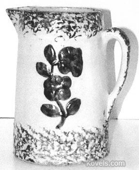 This blue and white pitcher has spongeware borders and a raised blue flower decoration. The 9-inch pitcher is worth over $250.