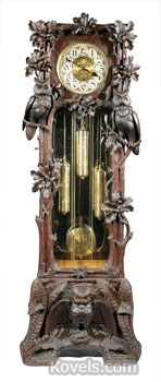 "Owls, oak leaves, acorns and ferns are carved on the sides and base of this tall case clock. The 7 1/2-foot-tall clock sold for $14,000. The works are marked ""Hawina,"" a German trademark."