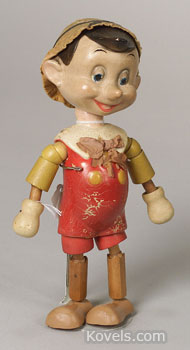 Pinocchio is a cheerful young boy in the Disney cartoon. This 11-inch-high segmented wooden doll was made by Ideal Toy Co. of New York City about 1940. It was auctioned by Skinner Galleries in Boston for $118 despite his repainted feet and worn paint.
