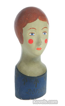 This early 20th-century French papier-mache milliner's head has original paint with some crazing. Her name,