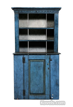 "Worn blue paint can be seen on this ""country"" cupboard. The top part is shallower than the bottom, giving it the name ""stepback cupboard."" It sold for $1,180 at a Brunk auction in Asheville, N.C."