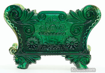 This rare lacy-period Sandwich glass open salt dish, 3 inches long, is in the Basket of Flowers pattern. Because it is in an unlisted emerald green color, it sold at Green Valley Auctions in Mt. Crawford, Va., for $10,450, a record price for a lacy salt.
