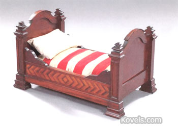 This is a mid-19th-century doll's bed made to hold a 24-inch doll on the 30-inch-long mattress. It is well made of mahogany with inlaid rails. It sold for the adult-sized price of $1,292 at New Orleans Auction Galleries.