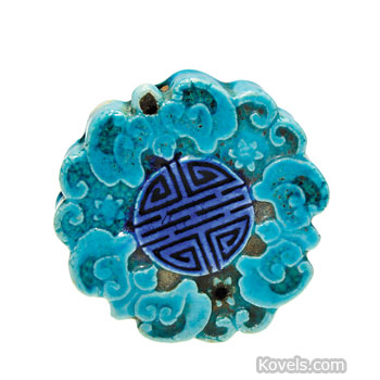 This piece of turquoise-glazed pottery, 2 inches in diameter, is covered with scrolls arranged around a seal. It is a
